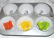 counting colored pasta in muffin tins