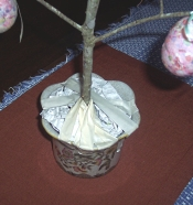 Taping the branch into the pot to make an Easter tree to hold ornaments.