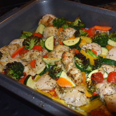 Roasted veggies and chicken cooked in pan.