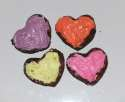 Small heart brownies with colored frosting.