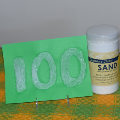 Make this sensory 100 day sign with sand.