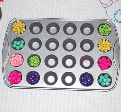 Sorting beads in muffin tins.